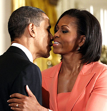 US President Barack Obama (L) kisses his wife first lady Michelle Obama
