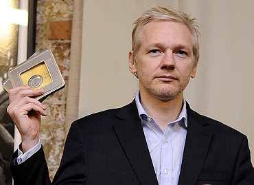 WikiLeaks founder Julian Assange holds up CD's containing data on offshore bank account holders