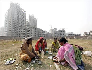 Labourers eat food at the site of a residential estate under construction in Kolkata