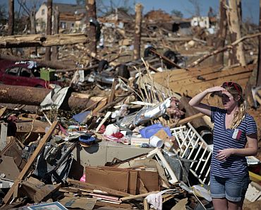 A woman looks over devastation in the aftermath of deadly tornados in Tuscaloosa, Alabama