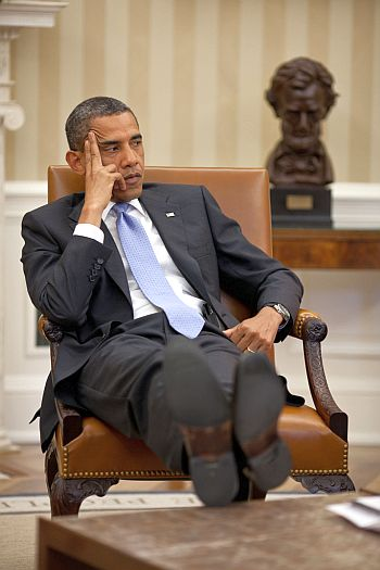 President Barack Obama listens during a meeting with advisors in the Oval Office