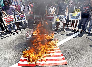 Protesters burn a replica of the US flag outside the US embassy