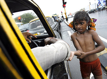 A little girl begs for alms in the rain in Mumbai
