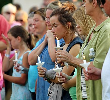 Members of the Copley community hold a candlelight vigil at Copley Community Park after the shooting spree