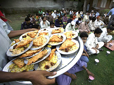 A man walks with a tray of donated food to serve to men breaking fast in the month of Ramadan in Lahore