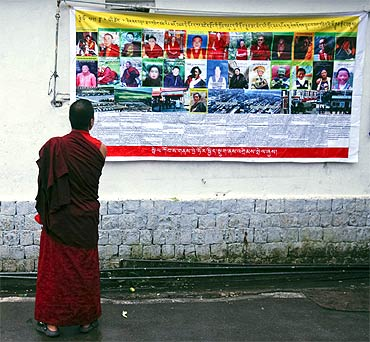 A Tibetan monk looks at a banner displaying pictures of what it said were Tibetan political prisoners in China, outside a monastery in Dharamsala