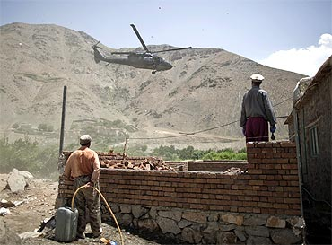 Afghans watch as a US Chinook helicopter leaves after a security handover ceremony in Panjshir province