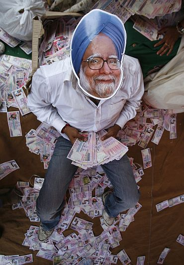 An activist wears a mask depicting Prime Minister Manmohan Singh