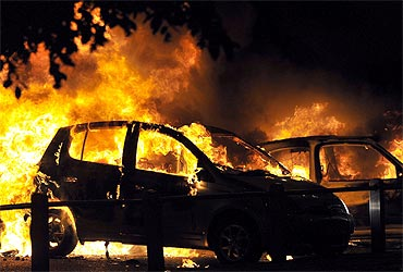 Cars burn on a street in Ealing, London, on Tuesday.