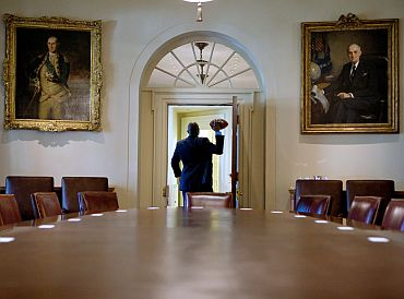 Framed by the doorway of the Cabinet Room, a personal aide throws a football to President Barack Obama
