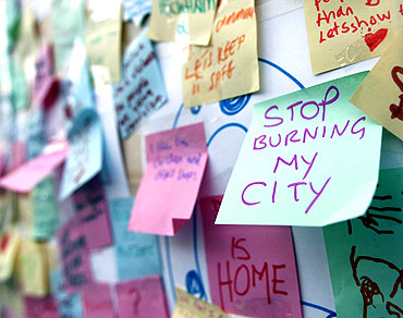 Hundreds of messages of support from the community of Peckham are seen posted on a looted storefront in south London