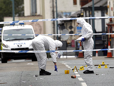 Forensics officers inspect the scene where three men were killed by a car in Winson Green area of Birmingham, central England