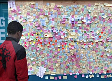 A youth looks at hundreds of messages of support from the community of Peckham posted on a looted storefront in southeast London