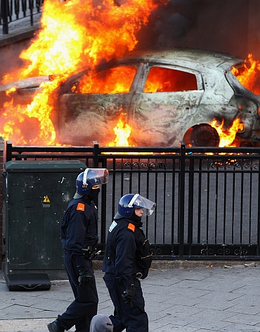Police walk past a burning car during riots