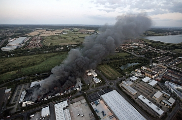 Smoke continues to rise from a Sony Warehouse which was destroyed by arsonists in Enfield in north London
