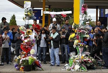 British Asians pray at the scene where three men were killed by a car during the recent rioting in the Winson Green area of Birmingham