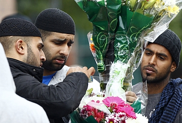Locals place floral tributes to Asian victims of the riots