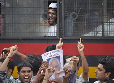A Hazare supporter shouts anti-government slogans from a police vehicle after being detained