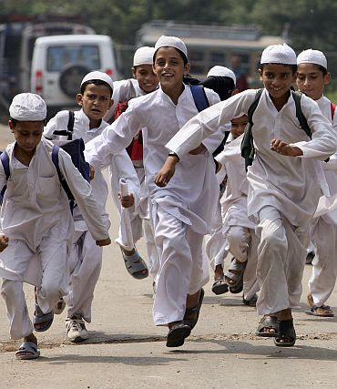 Boys run home from a  madrassa on the outskirts of Jammu