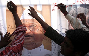 Supporters of Anna Hazare sign a banner outside Tihar jail