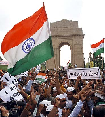 Supporters of Anna Hazare raise national flags during a protest march against corruption