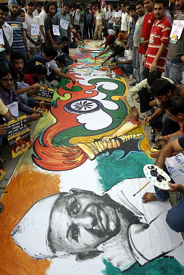 Supporters of Anna Hazare paint his sketch during a protest against corruption in Chandigarh