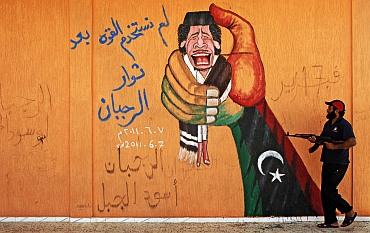 Anti-Gaddafi graffiti is seen on a wall near Yafran in eastern Libya