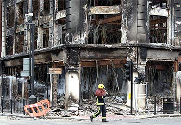 A fireman walks past the smouldering remains of a burnt out building after riots on Tottenham High Road in London.