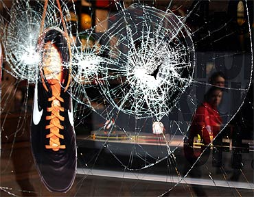 A shoe hangs in the smashed window of the Nike store in Manchester, northern England, after the riots