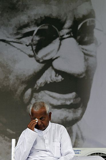 Anna Hazare wipes his eye in front of a portrait of Mahatma Gandhi