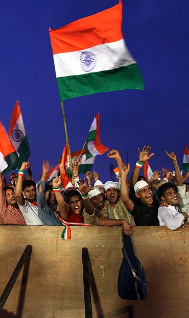 Supporters of Hazare shout slogans as they wave Indian national flags