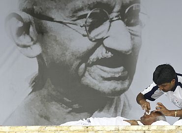 A supporter of Anna Hazare wipes his eyes during the ninth day of his fast at Ramlila Ground