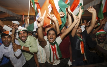 Supporters of Hazare shout pro-Hazare slogans as they celebrate after Hazare announced his decision to end his fast