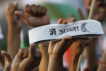 A supporter of Hazare holds a traditional Indian cap on which the words read: I am Anna