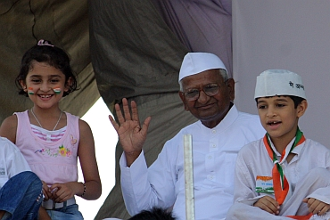 Hazare waves to crowds after breaking his fast