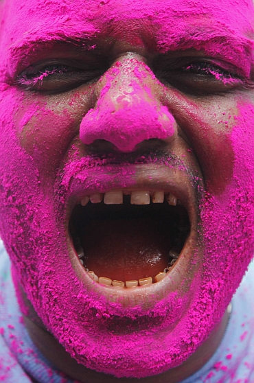 A supporter of Hazare, with his face smeared in pink colour, shouts pro-Hazare slogans during the celebrations