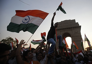 Hazare's supporters wave  national flags in front of India Gate