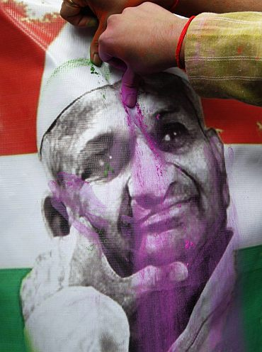 Supporters of activist Anna Hazare applies pink powder on the portrait of Hazare during the celebrations after Hazare ended his fast
