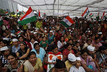 Supporters of Indian social activist Hazare wave Indian national flags at Ramlila grounds