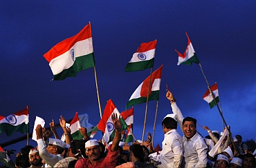 Supporters of veteran Indian social activist Anna Hazare shout slogans as they wave Indian national flags