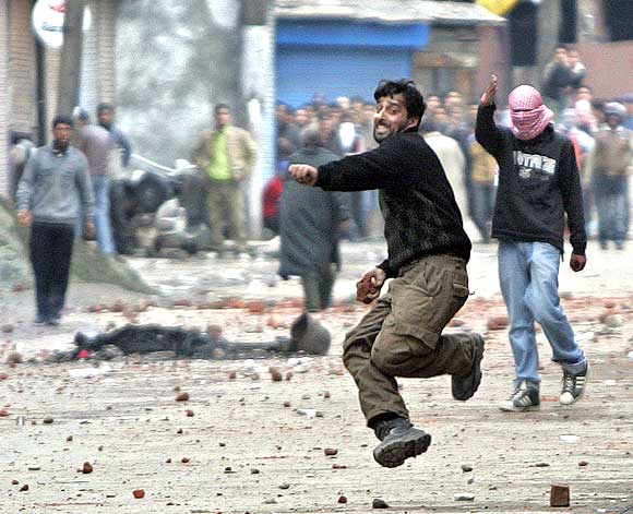 A Kashmiri protester hurls stones at Jammu and Kashmir policemen during a protest in Srinagar in 2010