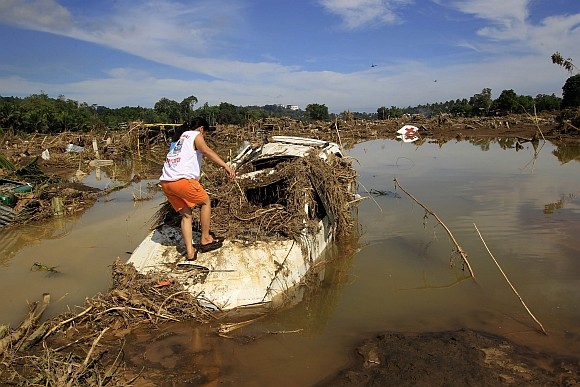 A woman inspects a submerged vehicle in a village hit by flashfloods brought by Typhoon Washi in Cagayan de Oro, southern Philippines