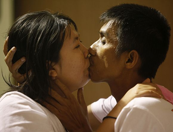 Participants Akekachai Tiranarat, 42, and his wife Raksana Taranarat, 31, kiss on their way to winning the World's Longest Continuous Kiss event in Pattaya, Bangkok