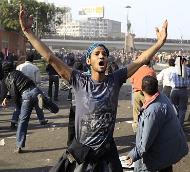 A demonstrator gestures during rioting between pro and anti-Mubarak supporters at Tahrir Square