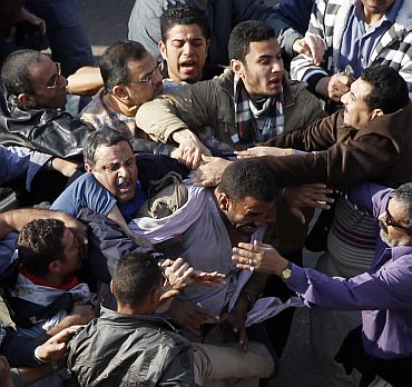 A pro-Mubarak supporter is held by anti-Mubarak demonstrators during clashes at Tahrir Square