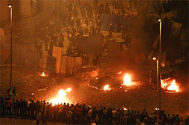 Pro-government protesters clash with anti-government protesters outside the National Museum near Tahrir square in Cairo