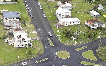 Houses with no roofs stand next to their undamaged neighbours after Cyclone Yasi