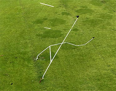 A set of rugby goal posts stand twisted by Cyclone Yasi