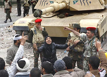 A female anti-government protester shouts slogans in front of army tanks near Tahrir Square in Cairo