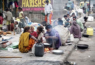 Homeless prepare their food by the roadside in Ahmedabad